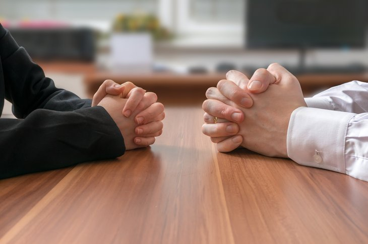 Two pair of clasped hands on a conference table.