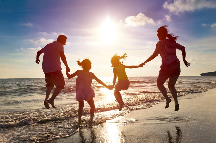 Family playing on beach, silhouette