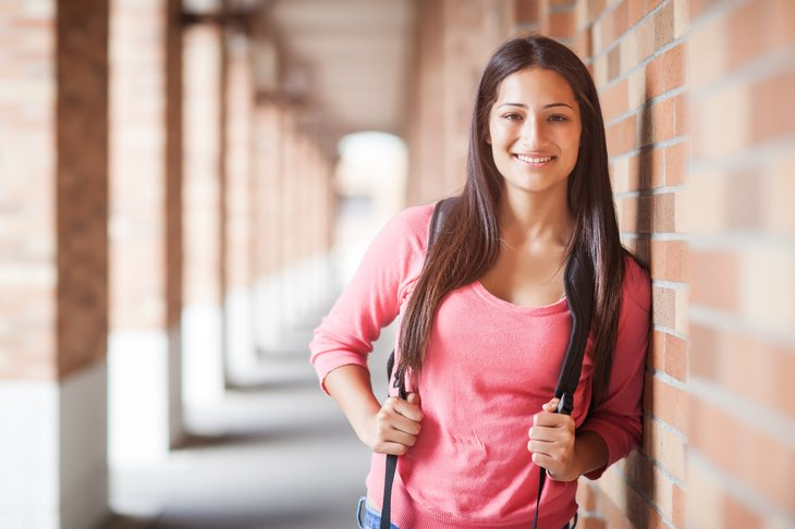 Young woman with backpack on campus.