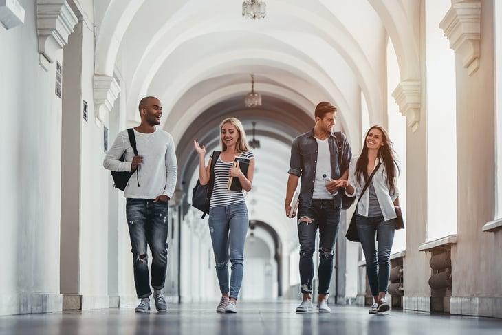 Students walk under outdoor archway.