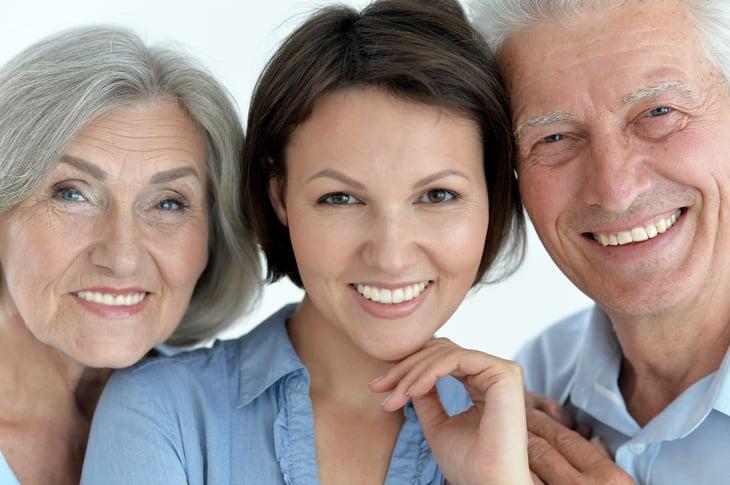 Portrait of older parents and adult daughter.