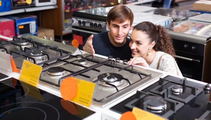 Couple looking at kitchen range.