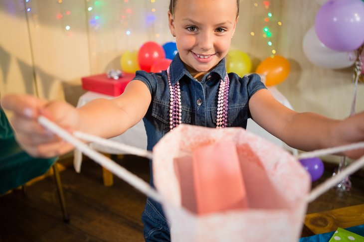 Girl at birthday party holding out gift bag.
