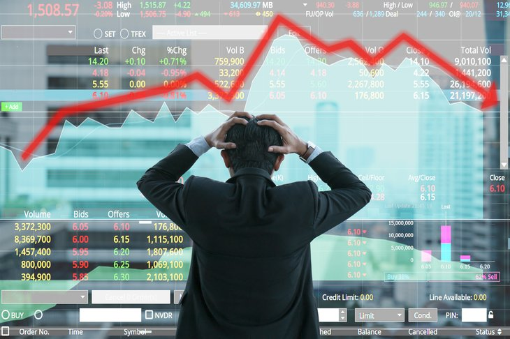 Man holds head, looking at stock chart.