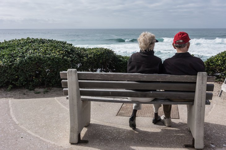 Older couple sitting on a bench overlooking the ocean.