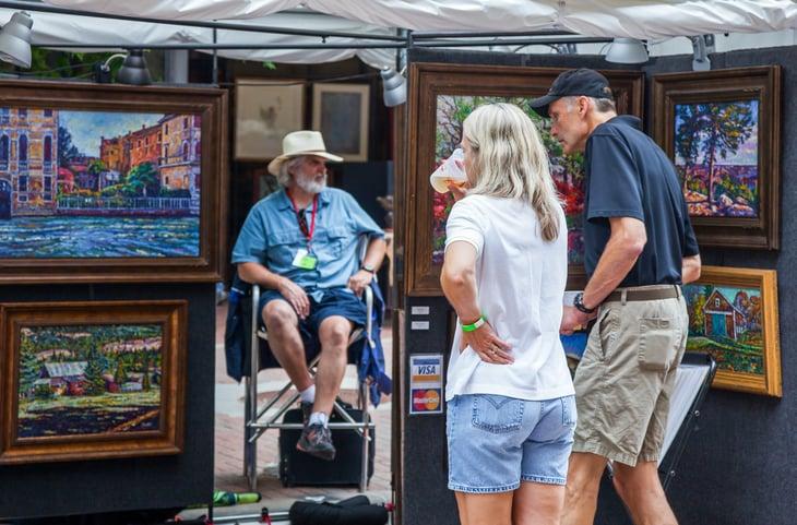 Older couple looking at art at street market.