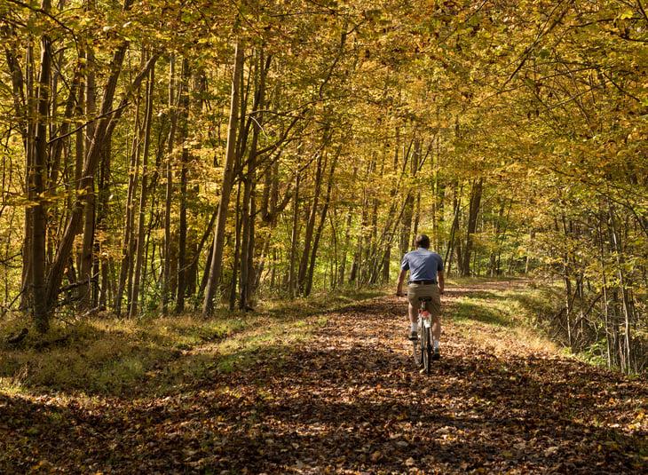 Older man biking in West Virginia woods.