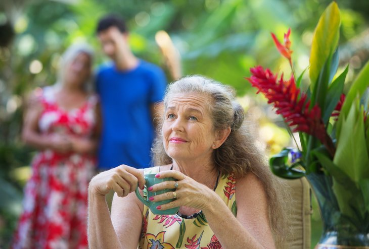 Older woman with cup of coffee in tropical setting.