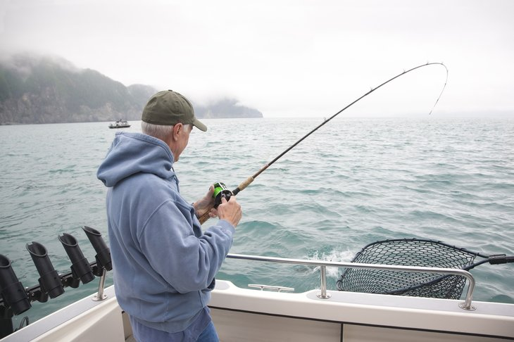 Senior man fishing off a boat in Alaskan waters.