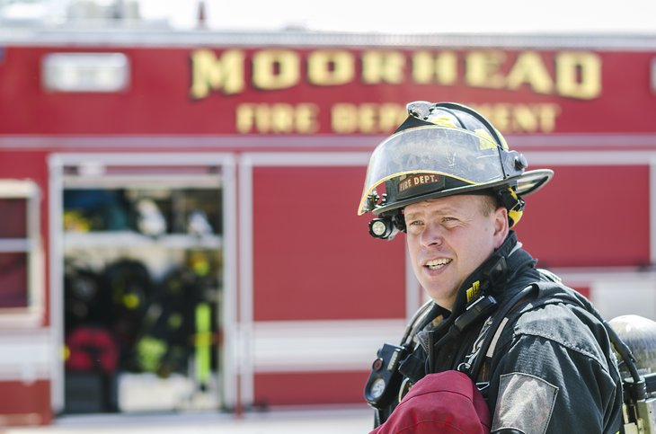 MOORHEAD, MN/USA - MAY 2, 2015: Fireman with the Moorhead Police Department in front of fire truck looking back on the scene where an alarm went off previously. - Image