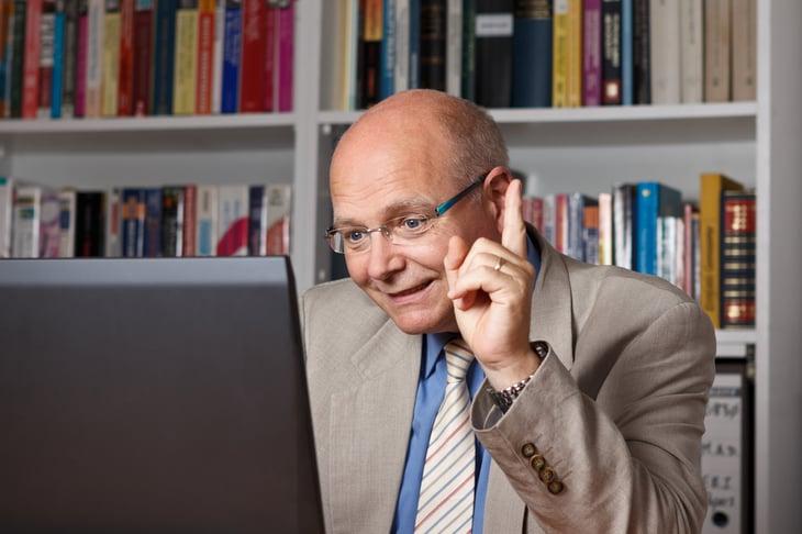 Elderly man giving class online.