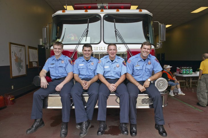 Four firemen sitting on front of fire truck in Americus Georgia