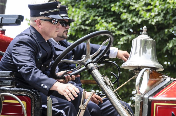 Bristol, Rhode Island, USA - July 4, 2011: Firefighters aboard antique fire engine at Independence Day parade in Bristol, Rhode Island