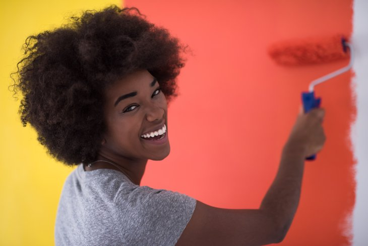 African American woman painting a wall.
