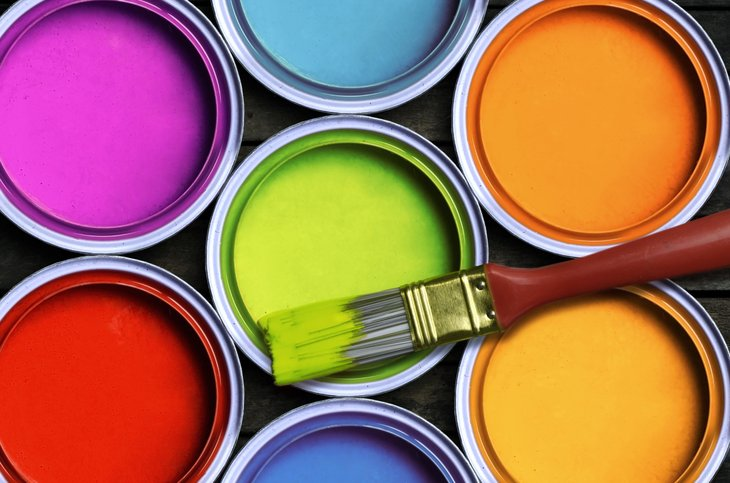 Open cans of paint containing bright colors.