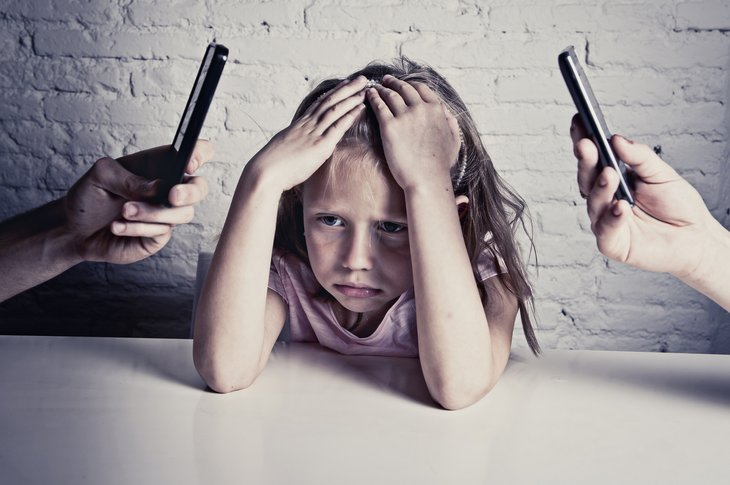 Frustrated child with parents on smartphones