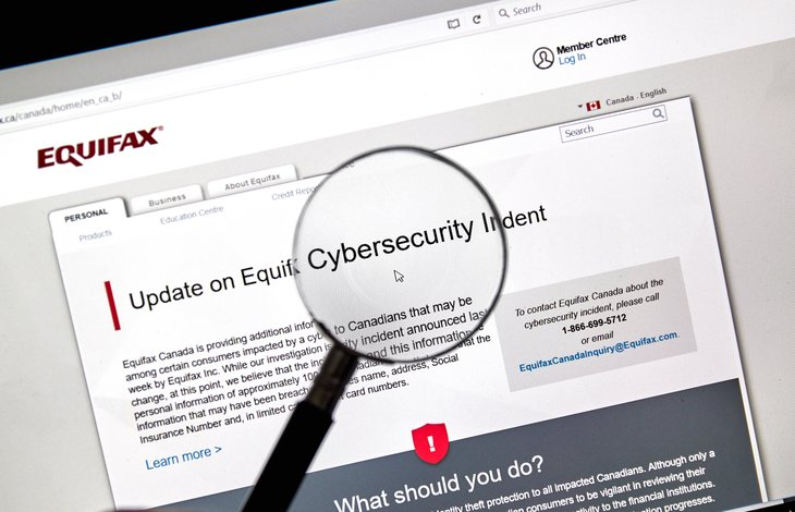 Magnifying glass and Equifax security breach alert online.