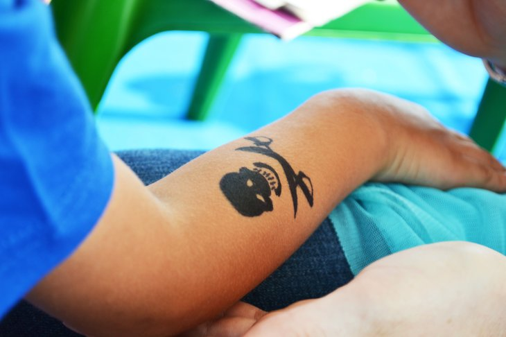 Child's arm with skull-crossbones temporary tattoo