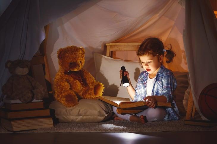 Boy reading by flashlight.