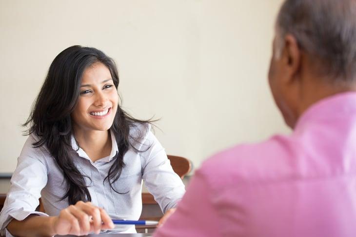 Woman and man talking across desk.