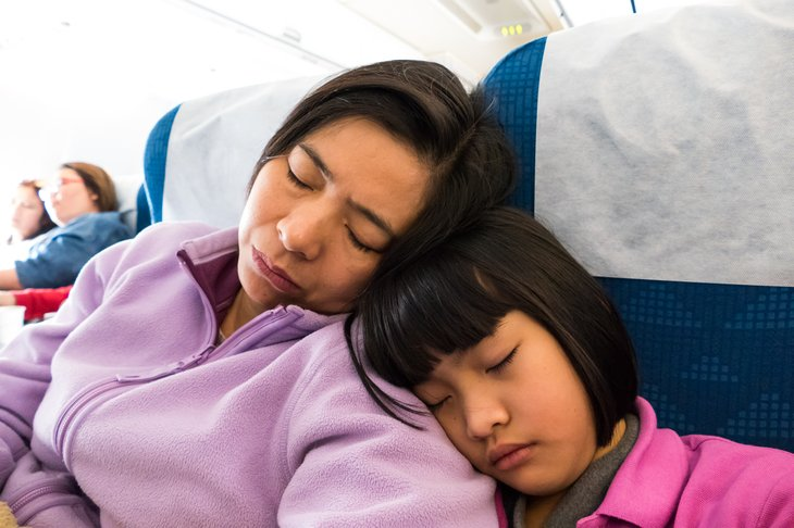 Mother and daughter sleeping on plane.