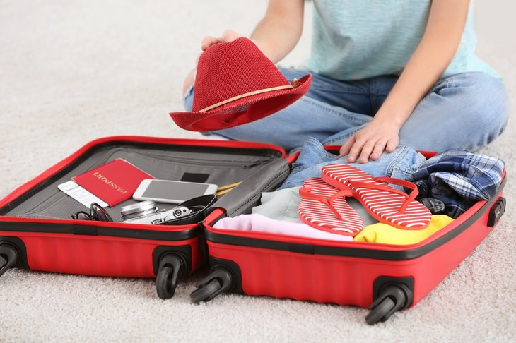 Woman packing suitcase.