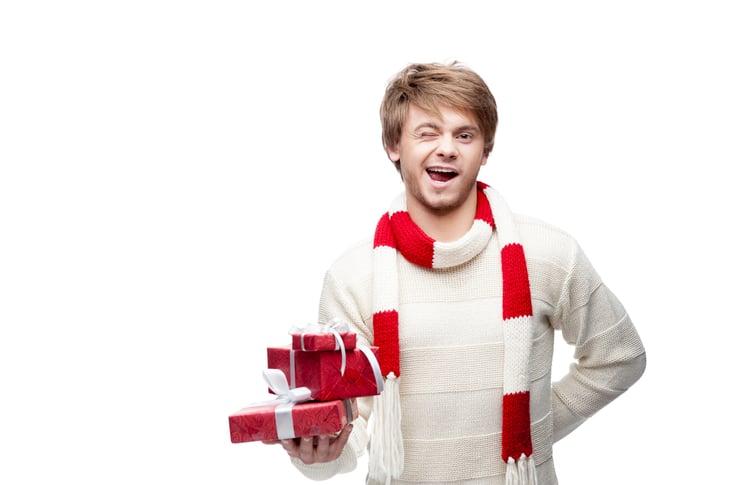 Man holding Christmas gift, winking.