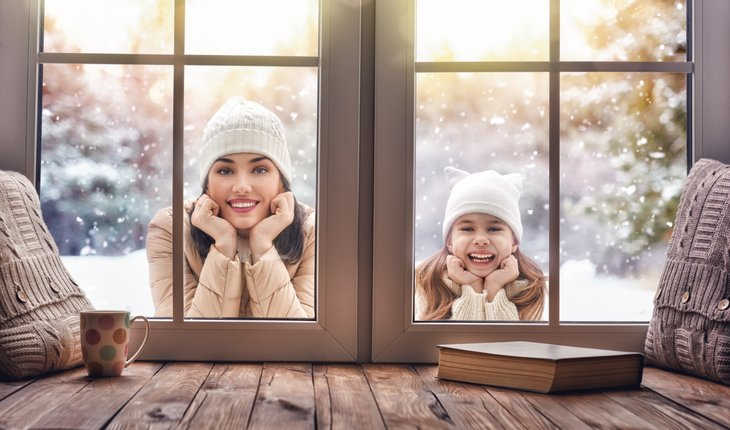 Woman and girl looking in window from winter scene.