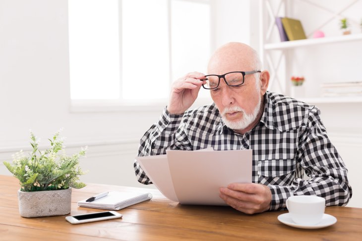 Older man looking at documents, with surprised expression,
