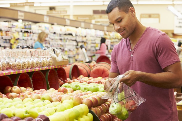 Man buying apples at a grocery store