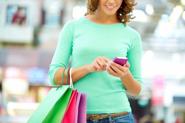 Woman with shopping bags, looking at cellphone