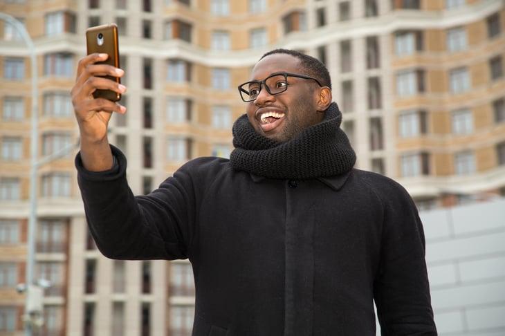Man doing a selfie on a city street.