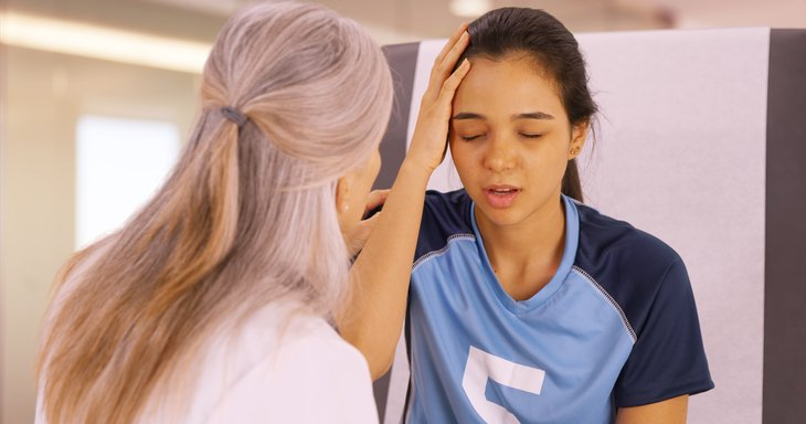 Soccer player consulting with doctor about head injury.