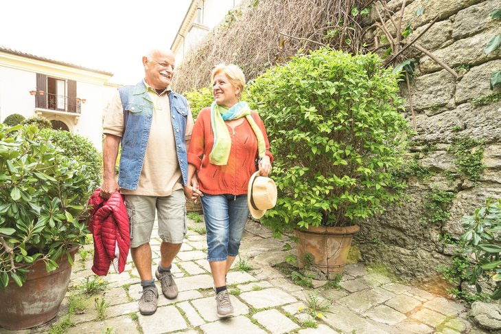 Older couple walking cobblestones in Italy.