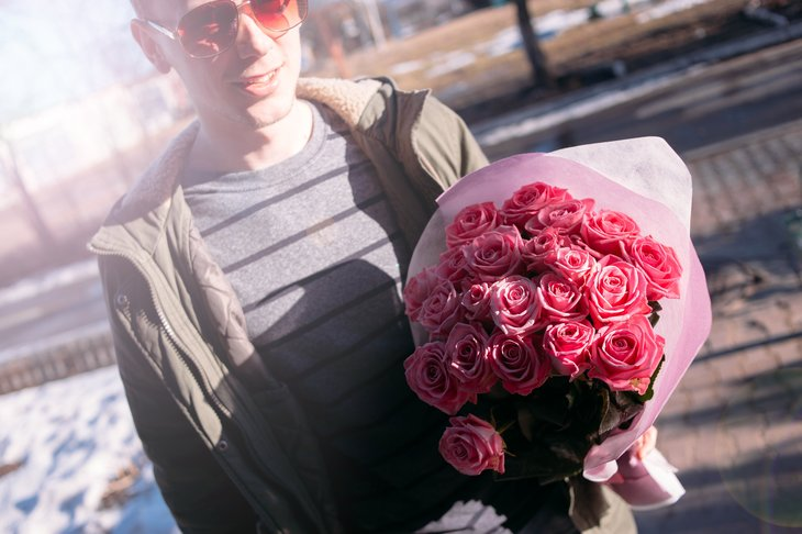 Young man with bouquet of pink roses.