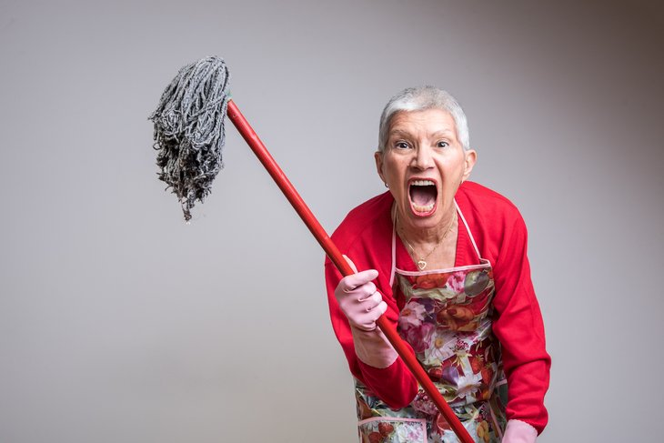 Angry woman wielding a mop.