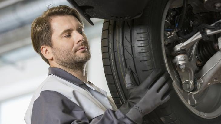 Man putting tire on car.