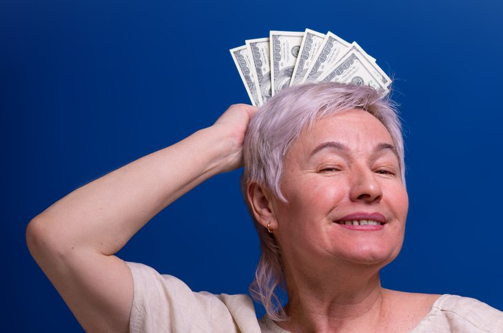 Smiling retired woman with money