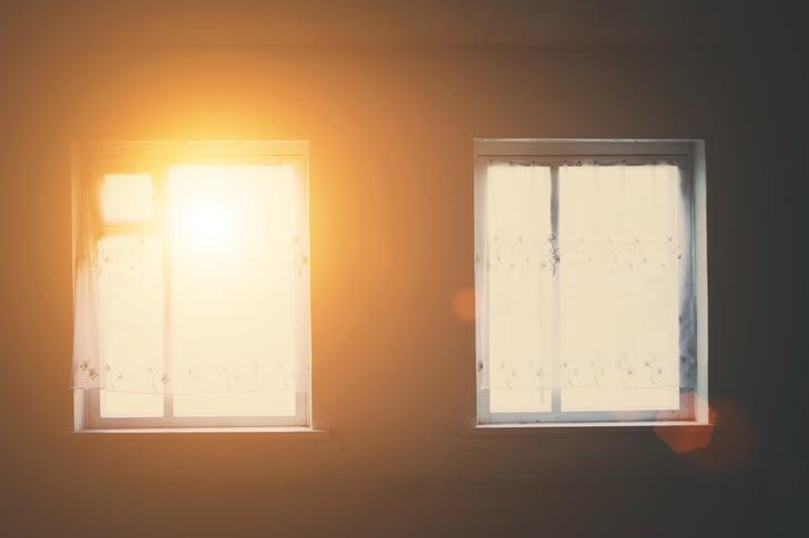 Windows with light shining through into dark room