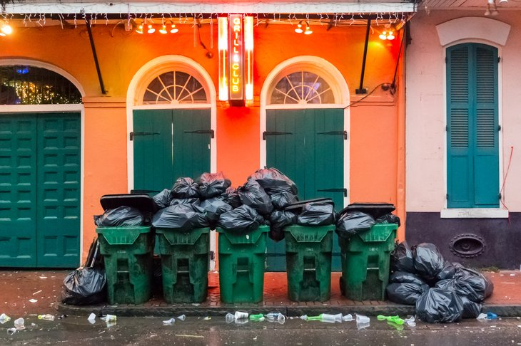Full garbage cans in front of a brightly lit shopfront