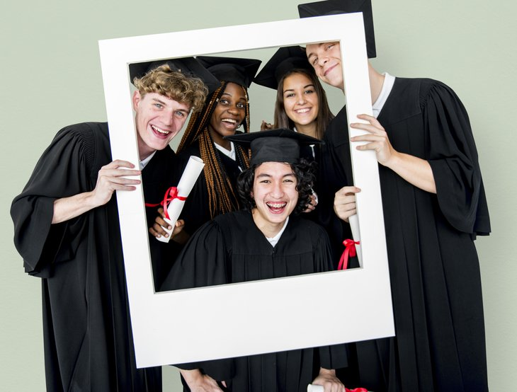 Graduates looking through a frame.