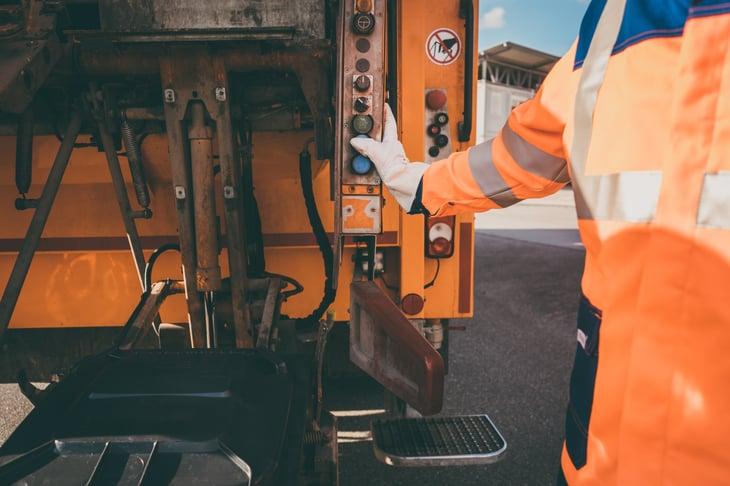 garbage removal worker emptying dustbin garbage truck
