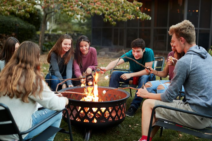 Teens roasting marshmallows around a firepit