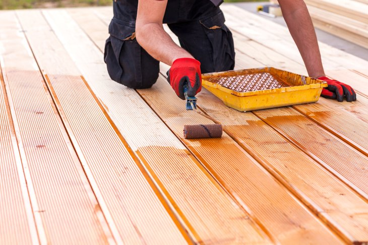 Person staining a wooden deck.