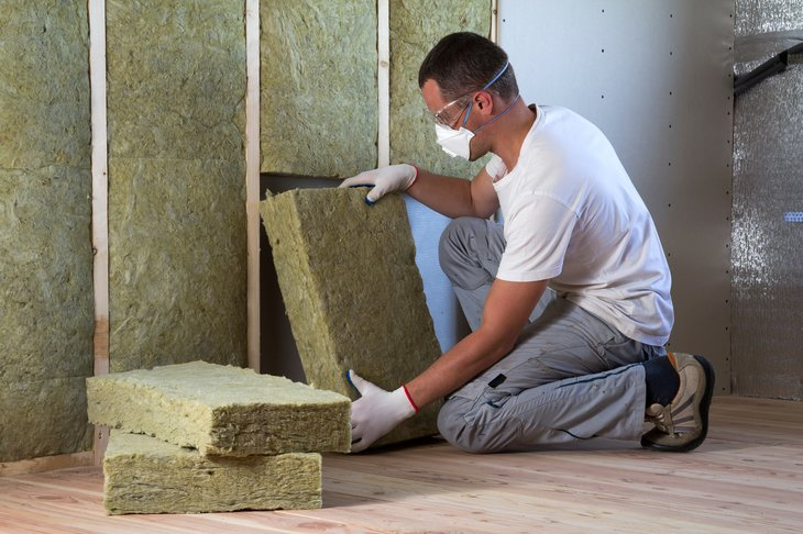 Worker insulating an attic