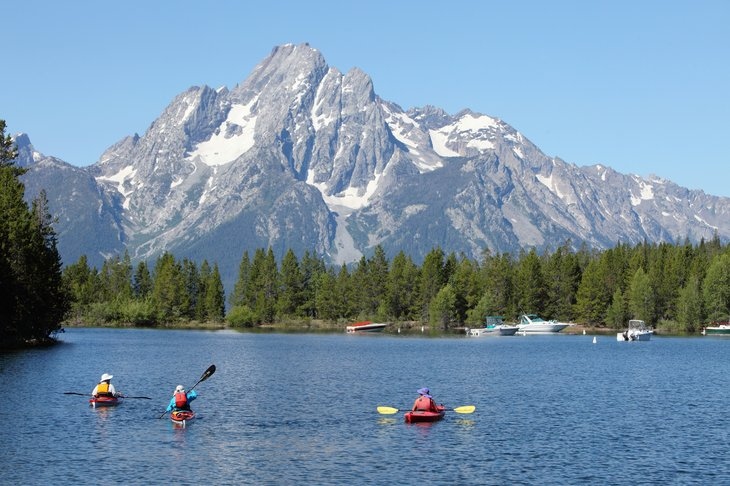 People kayaking on a lake with a mountain in the background.