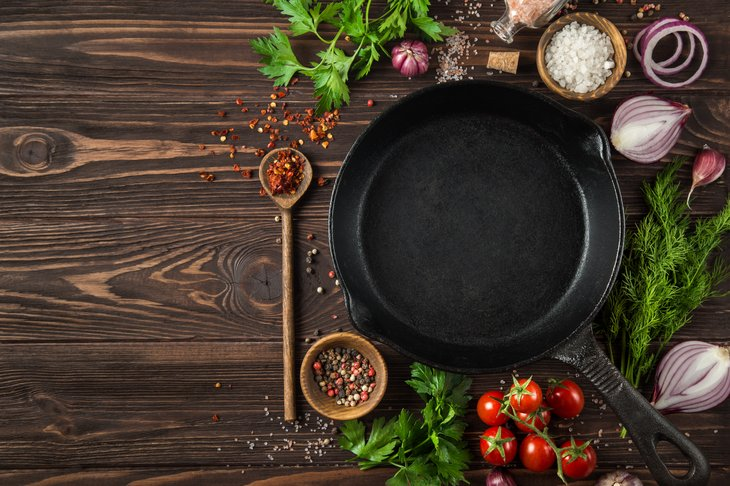 herbs and spices around cast iron skillet