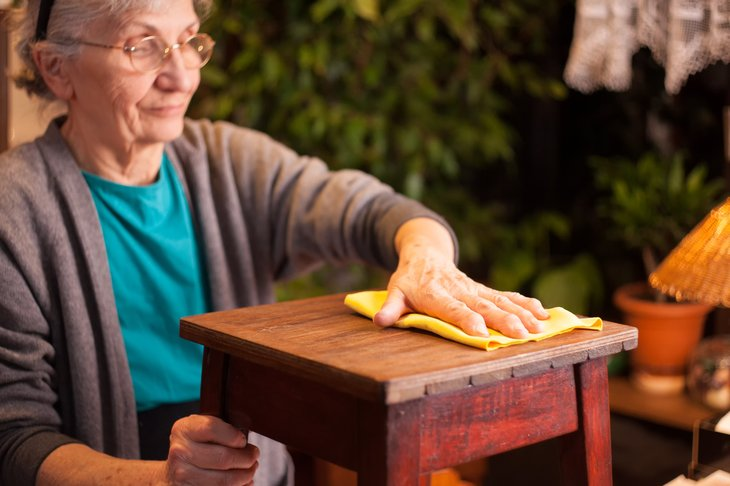 A senior woman cleans wood furniture