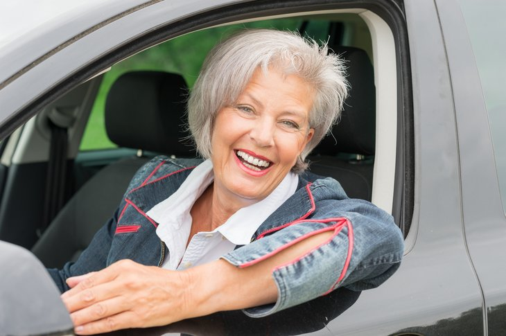 Woman at wheel of car.