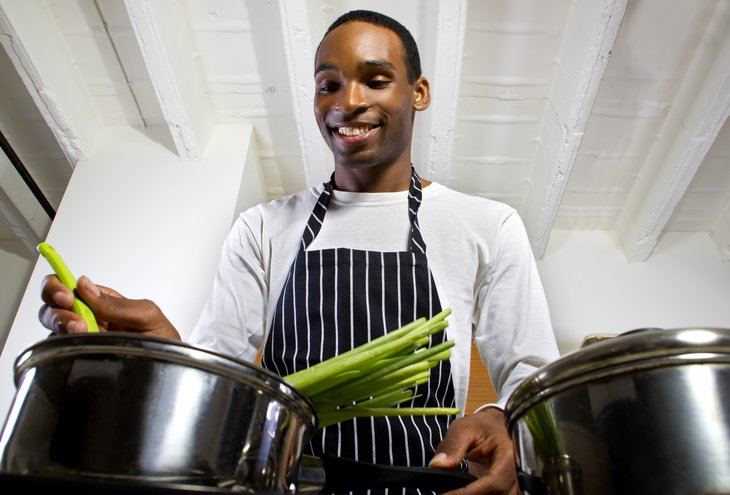 Young African American man cooking.